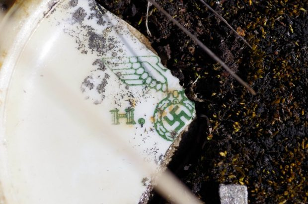"A fragment of a Nazi tableware produced by the ""Bohemia"" corporation. The piece was found on the surface of a burnt out building foundation at Sværholt in Finnmark. Photo: Stein Farstadvoll"